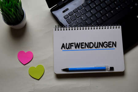 Aufwendungen write on a book isolated on office desk. German Language it means Operating Costs