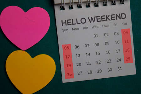 Top view Hello Weekend text on a Calendar isolated on office desk