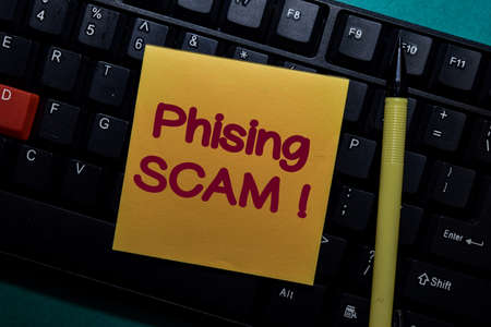 Phising Scam! write on a sticky note isolated on Office Desk