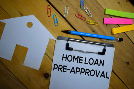Home Loan Pre-Approval write on a paperwork isolated on wooden background.