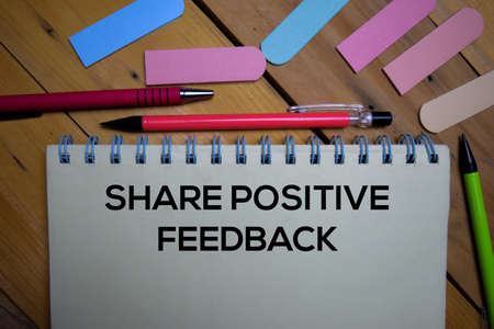 Share Positive Feedback write on a book isolated on wooden background.