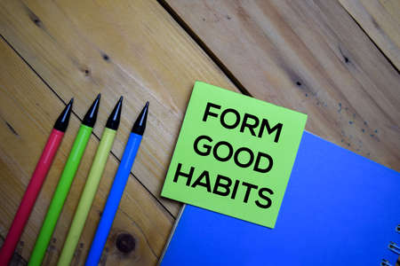 Form Good Habits write on a sticky note isolated on wooden background.