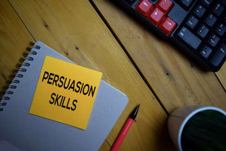 Persuasion Skills write on a sticky note isolated on wooden background.
