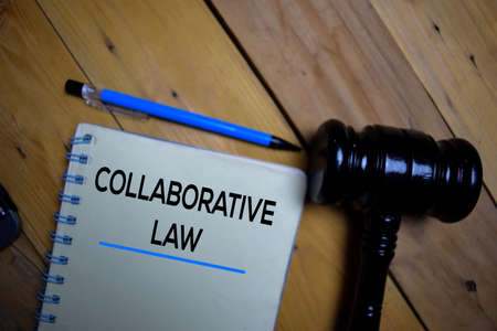 Collaborative Law write on a book isolated on wooden background. Selective focus on text Collaborative Law Stok Fotoğraf