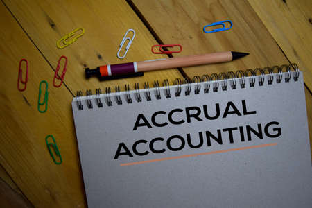 Accrual Accounting write on a book isolated on wooden background.