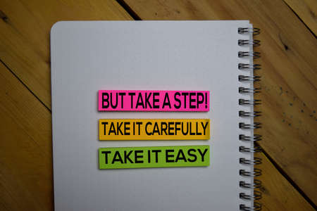 Take it East, Take it Carefully But Take a Step write on a sticky note isolated on wooden background.