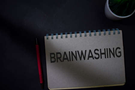 Brainwashing write on a book isolated on Office Desk
