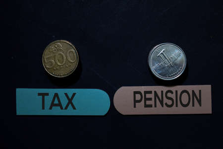 Tax or Pension and Indonesian Rupiah write on sticky note isolated on Office Desk