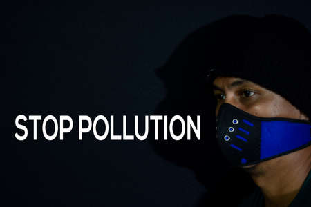 Bekasi. Indonesia. March 7 2020 : Young man use masker and stop pollution write on dark black background.
