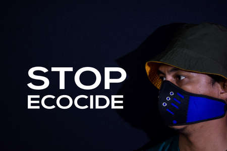 Bekasi. Indonesia. March 7 2020 : Young man use masker and stop ecocide write on dark black background. Stok Fotoğraf