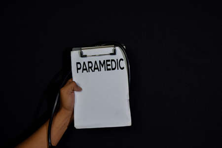 Paramedic write on paperwork isolated on dark black background. healthcare or medical concept