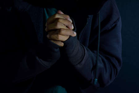 Young man worship and pray in cruch on dark black background. Christian faith or god concept. selective focus on finger Stok Fotoğraf