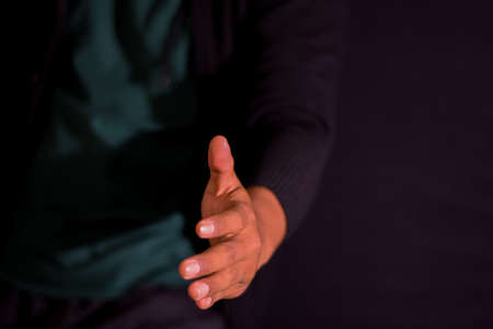 Young man giving hand for shaking on dark black background. selective focus on finger