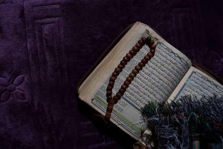 A Holy Quran, Prayer beads and turbans on the purple Prayer rug. Eid mubarak or islamic concept