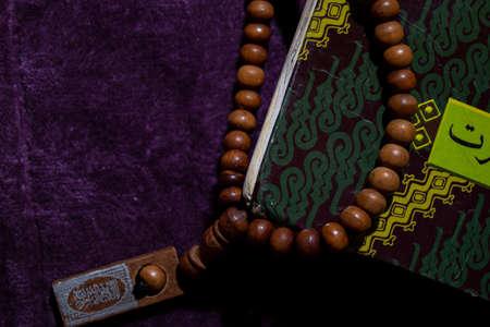 A Holy Quran and Prayer beads on the purple Prayer rug. Eid mubarak or islamic concept Stok Fotoğraf