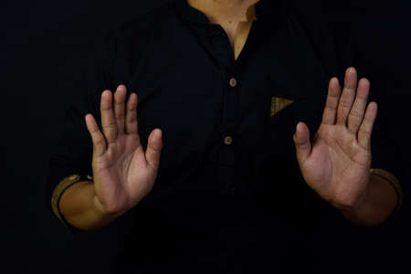 Asian man muslim takbir and solat take his hands up. Islamic praying concept on black background. Selective focus on arms and finger