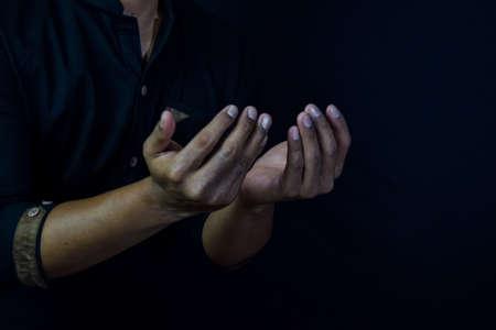 Half length view prayer of muslim Asian man. Islamic praying concept on black background. Selective focus on finger