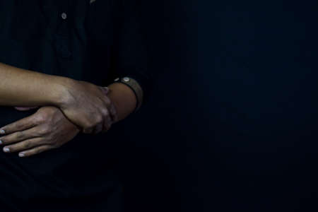 Young man praying with arms across posture. Islamic praying concept on black background. Selective focus on finger
