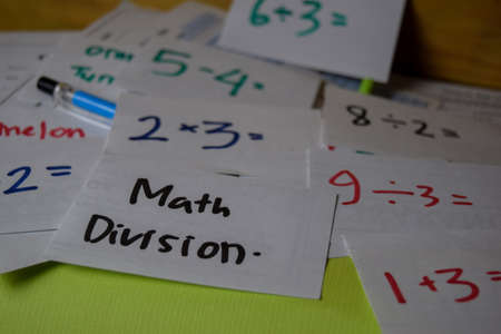 Math Division write on a sticky note isolated on Office Desk. Education concept