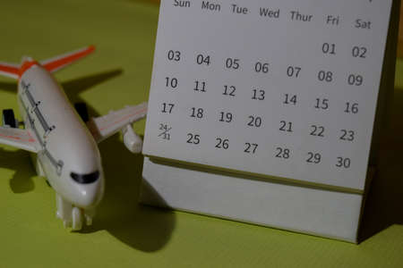 monthly Calendar and airplane toys isolated on office desk