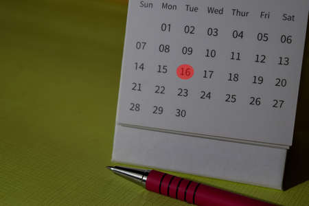 monthly Calendar and marked 16th isolated on office desk Stok Fotoğraf