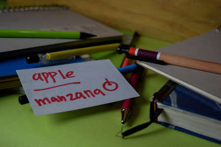 Manzana write on a sticky note isolated on Office Desk. Learning Spanish Language concept