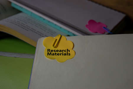 Research Materials write on a sticky note isolated on Office Desk. Business Document concept