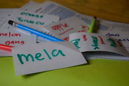 Mela write on a sticky note its mean apple isolated on Office Desk. Learning Italian Language concept