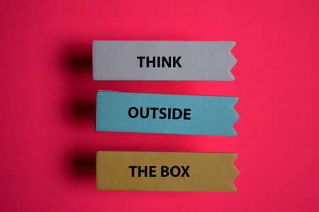 Think Outside The Box write on a sticky note isolated on Office Desk. Stok Fotoğraf