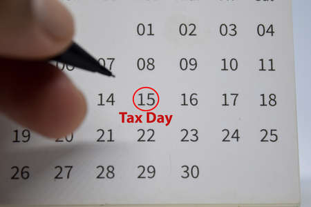 Tax Day on monthly Calendar and marked 15th isolated on office desk