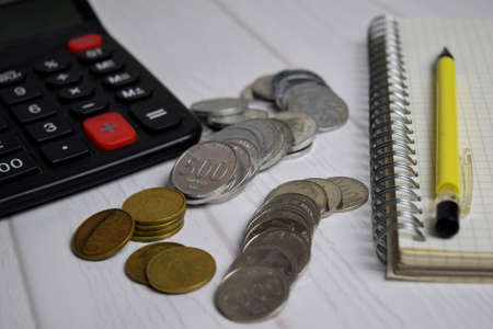 Calculator and the stack of coint isolated on office desk. calculating salary or tax concept