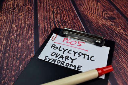 PCOS. Polycystic Ovary Syndrome write on sticky notes. Isolated on wooden table background