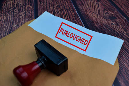 Red Handle Rubber Stamper and Furloughed text Isolated on wooden table background