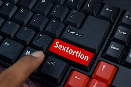 Sextortion isolated on laptop keyboard background.