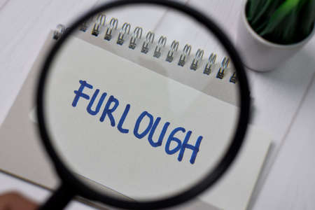 Furlough write on sticky notes with magnifying glass isolated on office desk