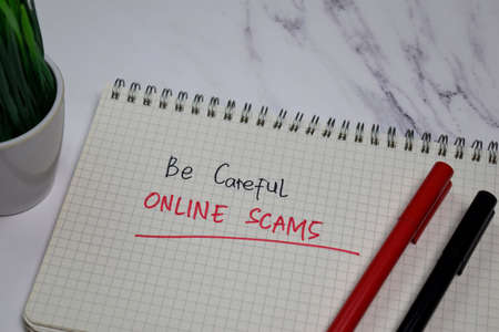 Be Careful Online Scams write on a book isolated on office desk