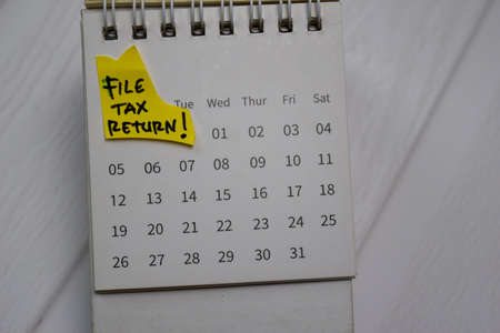 File Tax Return text on monthly Calendar isolated on office desk