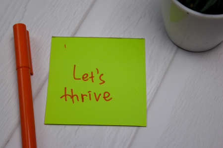 Let's Thrive write on sticky note isolated on wooden table. Фото со стока