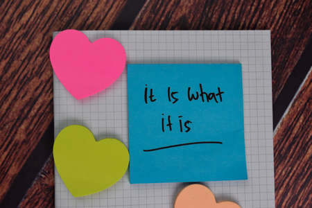 It is What It Is text on sticky notes with office desk.