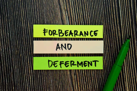 Forbearance and Deferment write on sticky notes isolated on Wooden Table. 版權商用圖片