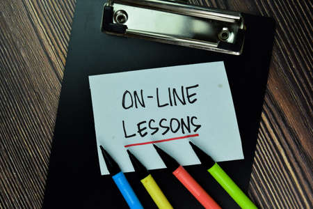 On-Line Lesson write on sticky note and isolated on Wooden Table. Educational Concept Stockfoto