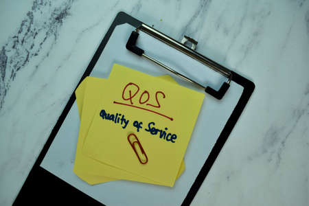 QOS - Quality of Service write on sticky note isolated on Wooden Table. Business Concept
