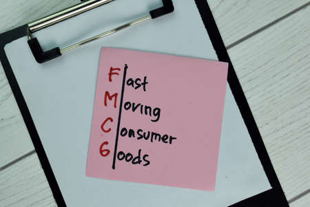 FMCG - Fast Moving Consumer Goods write on sticky note isolated on Wooden Table.