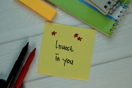 Under Promise and Over Deliver write on sticky note isolated on Wooden Table.