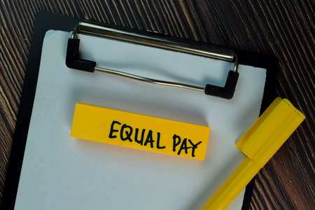 Equal Pay write on sticky notes isolated on Wooden Table.