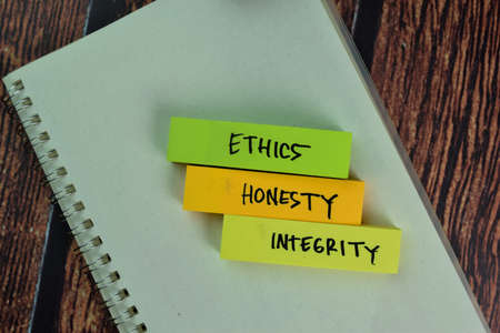 Ethics, Honesty, Integrity text on sticky notes isolated on green desk. Mechanism Strategy Concept