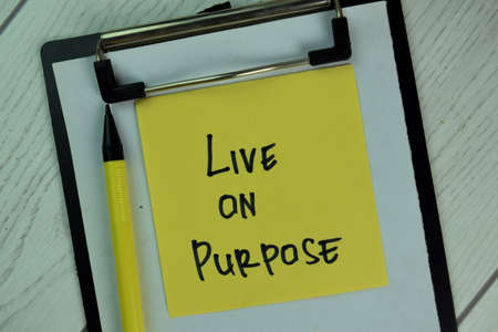 Live on Purpose write on sticky notes isolated on Wooden Table. Imagens
