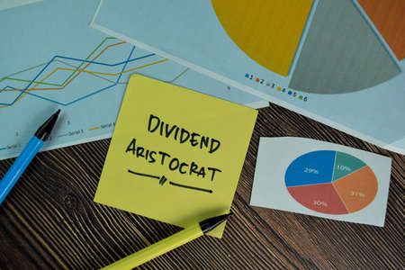 Dividend Aristocrat write on sticky notes isolated on Wooden Table.