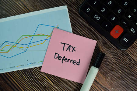 Tax Deferred write on sticky notes isolated on Wooden Table.