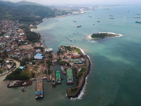 Aerial view of pelabuhan merak is a marine port and town harbor island of merak in the sunlight morning. Ferry boats, with noise cloud and cityscape. Banten, Indonesia, March 3, 2021